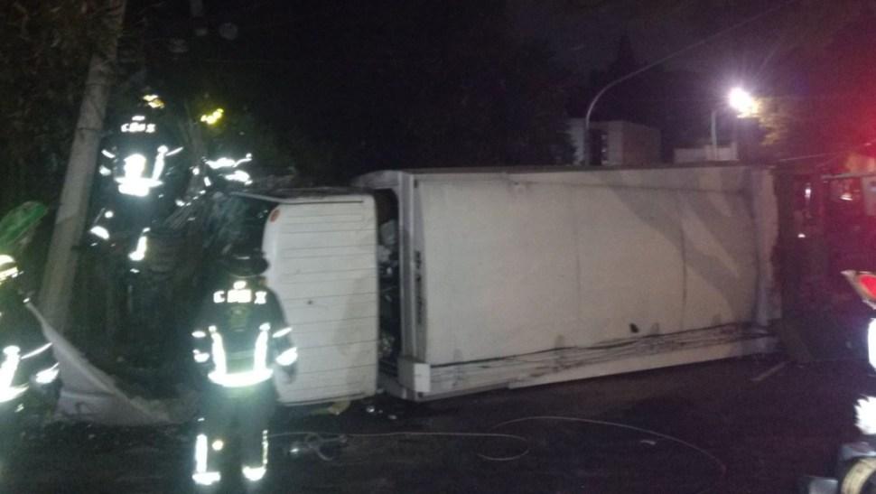 Foto: El conductor de un camión de basura perdió el control del vehículo y volcó sobre un camellón, 27 junio 2019