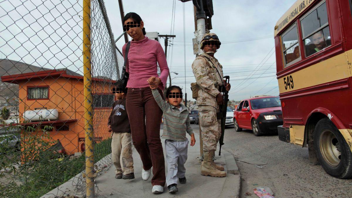Foto: Una mujer con hijos camina junto a un soldado cerca de un puesto de control militar en Tijuana, México. El 16 de enero de 2010