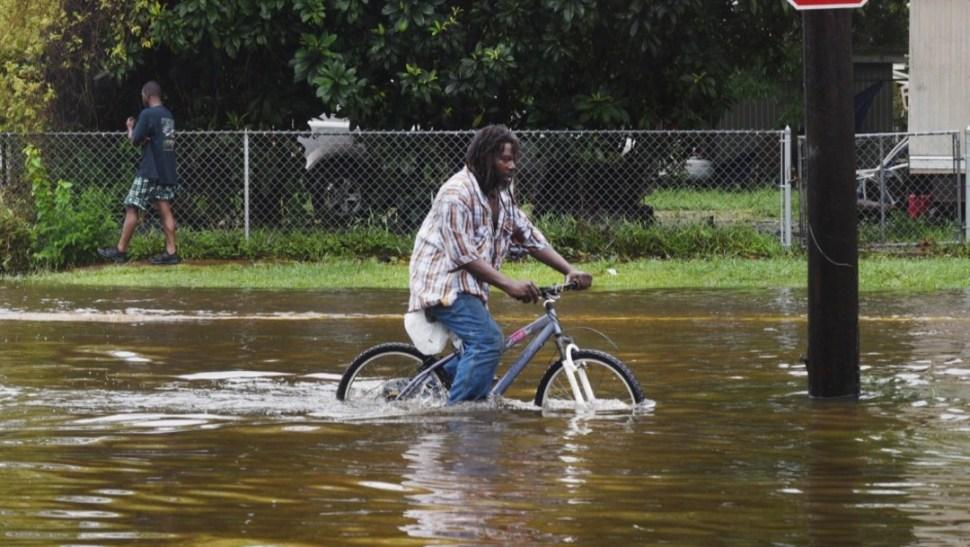 Foto: Un hombre intenta avanzar en una bicicleta a través de las aguas de la tormenta tropical Barry en Nueva Iberia, Louisiana, julio 14 de 2019 (Reuters)