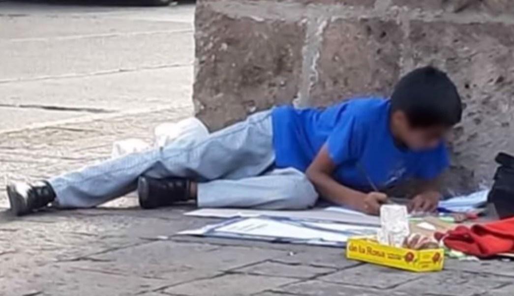 foto Recibe beca niño vendedor de dulces que hacía tarea en la calle 12 julio 2019