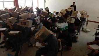 Foto Maestro pone cajas de cartón en la cabeza a alumnos para evitar que copien 29 agosto 2019