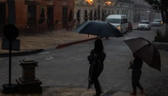 Foto: Dos personas se protegen de la lluvia, 25 agosto 2019