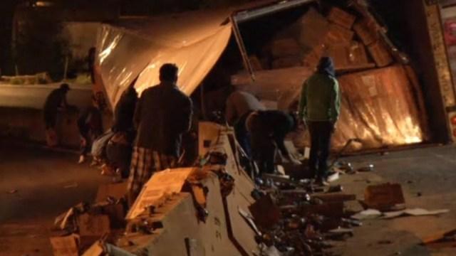 Foto: El tráiler volcó sobre su costado izquierdo y la caja quedó parcialmente destrozada al caer sobre la barrera de contención, 25 de agosto de 2019 (Noticieros Televisa)