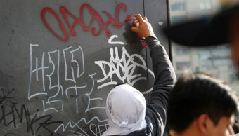 Joven realiza pintas durante la marcha, 02 octubre del 2019 (Reuters)