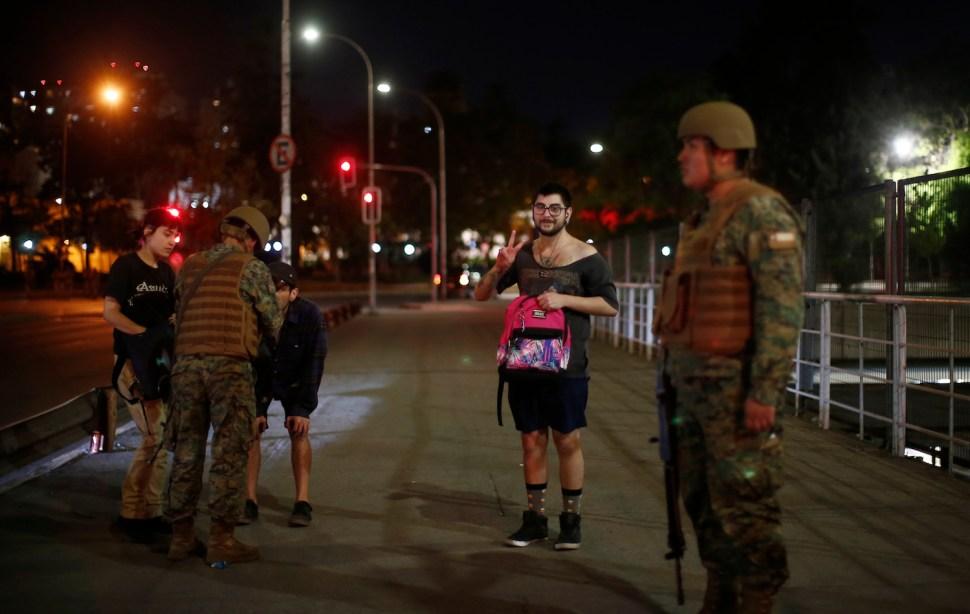 Santiaguinos siendo revisados por soldados en retén en medio de toque de queda en Santiago