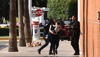 Foto: Una mujer corre con su hijo en brazos durante las balaceras en Culiacán, Sinaloa, el 18 de octubre de 2019 (Cuartoscuro)