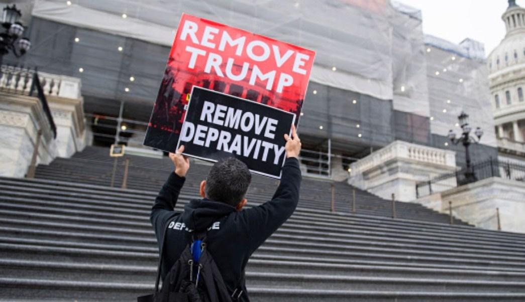 """Foto: Un joven carga carteles con la leyenda """"Remove Trump, Remove Depravity"""" en la escalinata del Capitolio. Getty Images"""