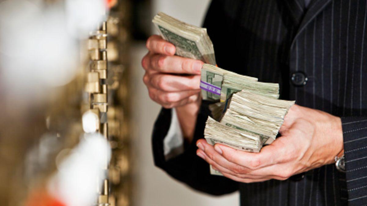 Foto: Un hombre cuenta fajos de billetes