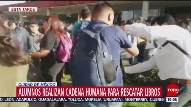 FOTO: Alumnos realizan cadena humana para rescatar libros de vandalismo en la UNAM, 14 noviembre 2019