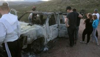 Miembros de la familia LeBarón observan un vehículo calcinado
