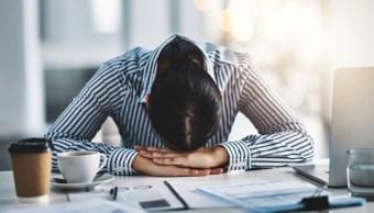 Foto: Una oficinista descasa en el escritorio de su trabajo. Getty Images/Archivo