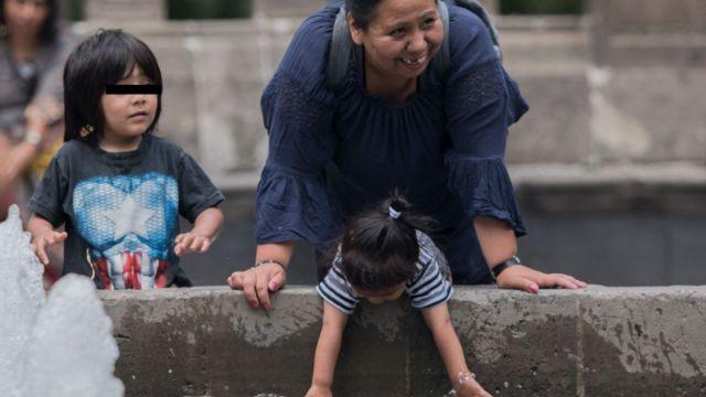 Foto: Una madre juego con sus hijos en una fuente de la Alameda Central en la Ciudad de México. Cuartoscuro