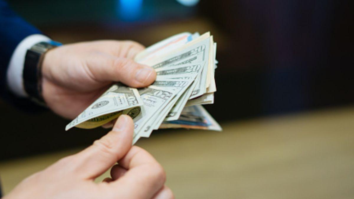 Un hombre cuenta varios billetes de 20 dólares. Getty Images  Archivo