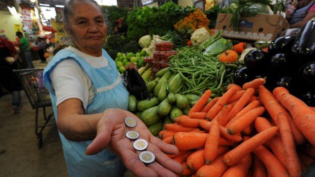 Foto: Una señora muestras unos pesos al comprar verdura en un mercado. Cuartoscuro