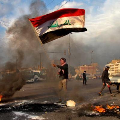Foto: Un hombre ondea la bandera de Irak durante protestas contra ataque de misiles iraníes en Bagdad, el 10 de enero de 2020 (AP)