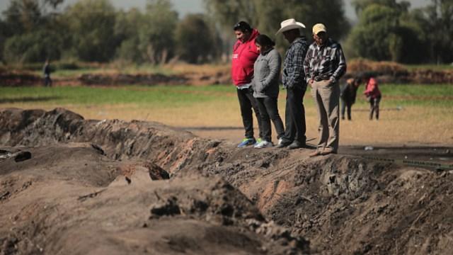Foto: Los familiares de una de las víctimas buscan objetos entre las cenizas tras la explosión de una toma clandestina