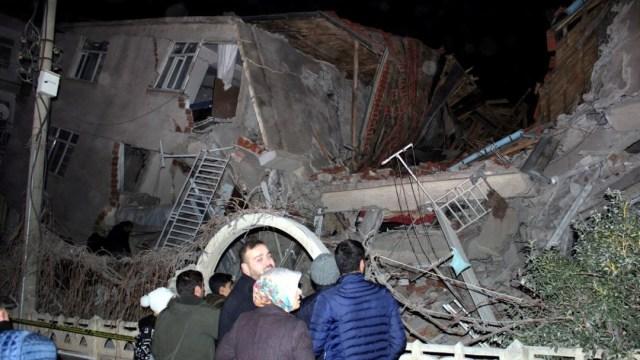 Foto: Un grupo de personas se paran frente a un edificio derrumbado en Elazig, Turquía, el 24 de enero de 2020 (Reuters)
