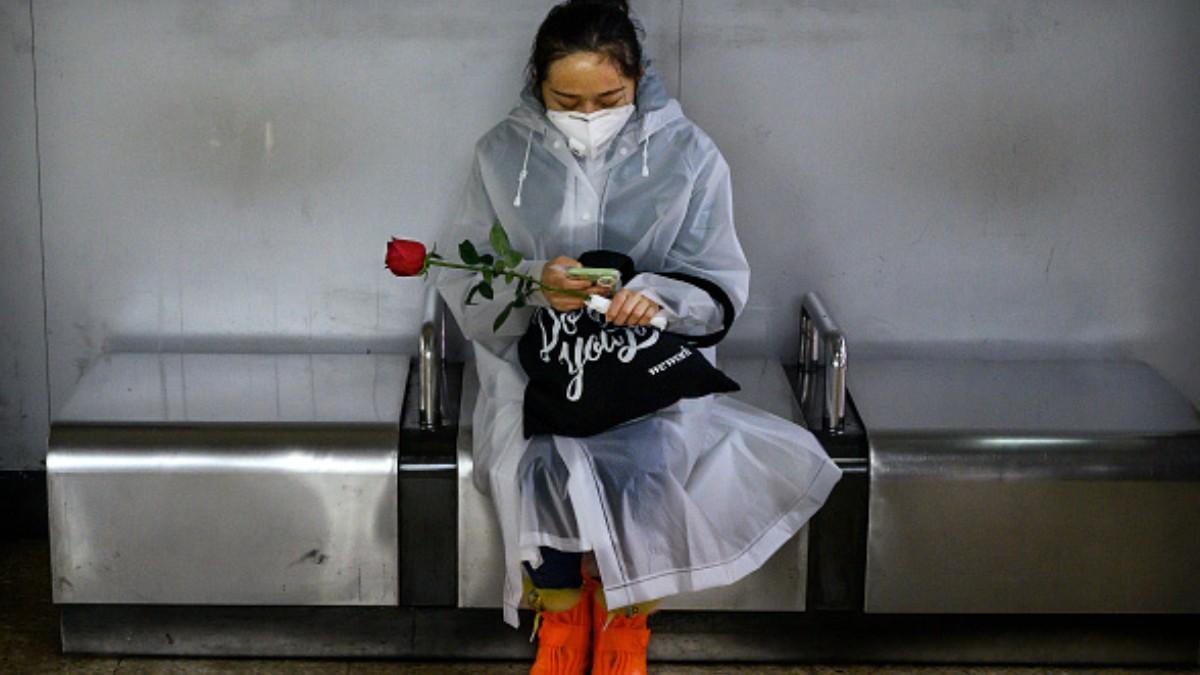 Foto: Una mujer china observa su celular cargando una rosa. Getty Images