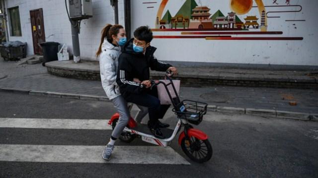 Foto: Dos jóvenes andan en motocicleta por calles de Beijing, China. Getty Images