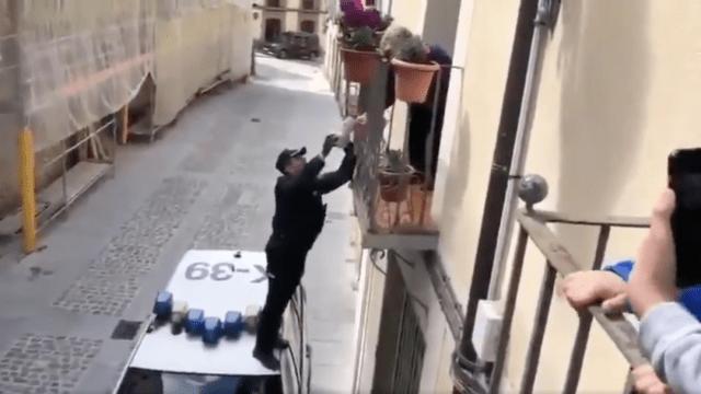 Foto Policía trepa a balcón para entregarle regalo de cumpleaños a anciana en España 30 marzo 2020