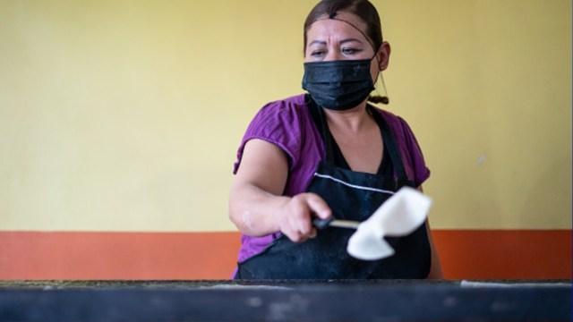 Foto: Una señora usa cubreboca mietras hace tortillas. Getty Images