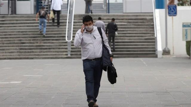Foto: Un hombre camina por calles de Puebla usando cubre boca. Cuartoscuro