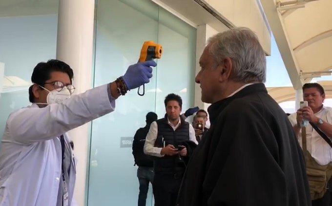 Foto: ¡Tengan! dice AMLO tras tomarse la temperatura en Oaxaca, 1 de abril de 2020, (Twitter @VGalvezMx)