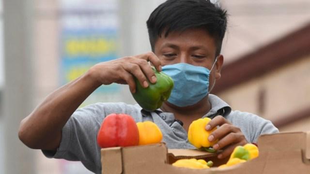 Foto: Un comerciante usa cubreboca. Getty Images