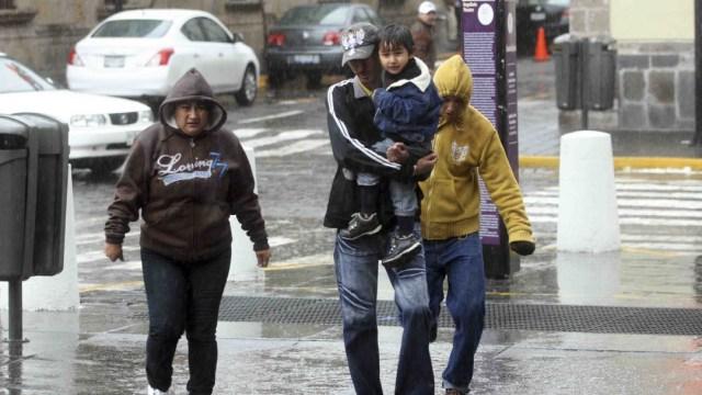 Una familia camina bajo la lluvia. (Foto: Cuartoscuro)