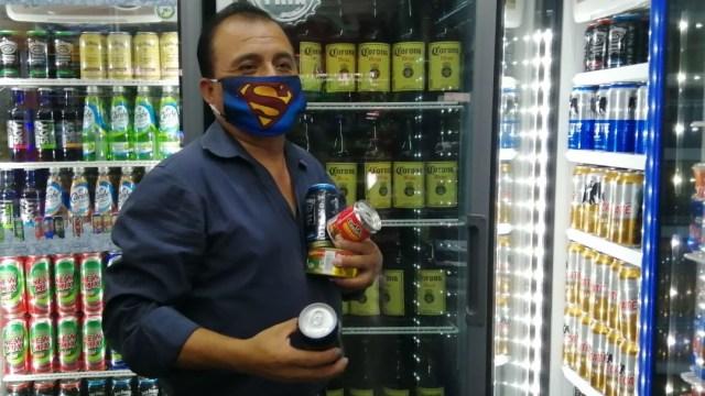 Un hombre con cubrebocas carga unas latas de cerveza y comida. Cuartoscuro