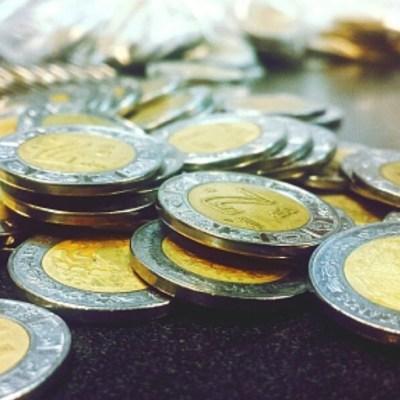 Tiran en una mesa monedas de dos pesos y un peso mexicano. Getty Images