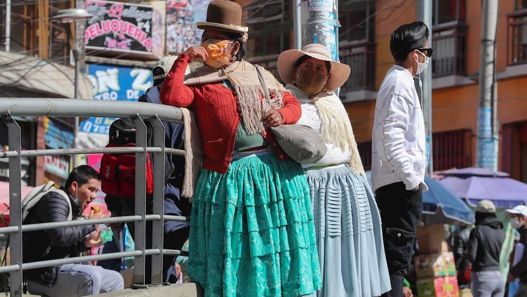 Mujeres aymaras con tapabocas son vistas en una plaza céntrica de La Paz, Bolivia. (Foto: EFE)