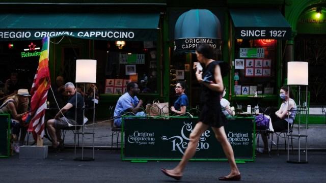 Mujer caminando frente a restaurante en Nueva York; Economía Estados Unidos