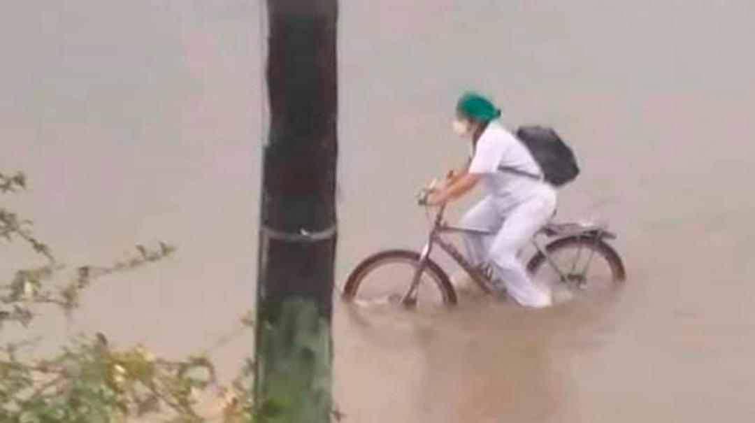 Enfermera en bicicleta durante inundación en Bolivia