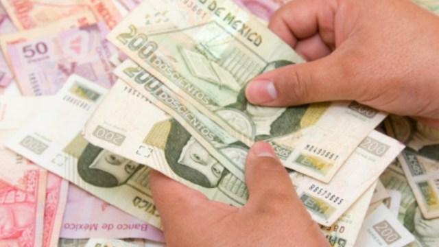 Un hombre sostiene con las manos billetes de 200 pesos. Getty Images