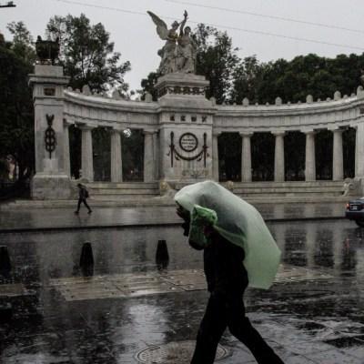 Un hombre se cubre con una bolsa mientras camina sobre avenida Juárez mientras permanecen las fuertes lluvias en la CDMX. (Foto: Cuartoscuro)