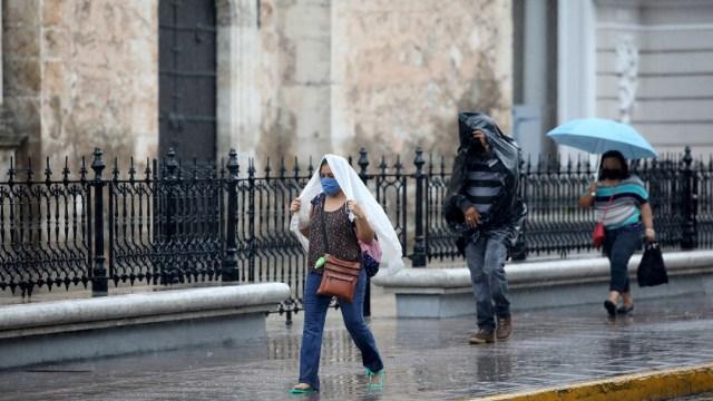 Las personas se protegen de la lluvia que se registra en algunos estados de México. (Foto: Cuartoscuro)