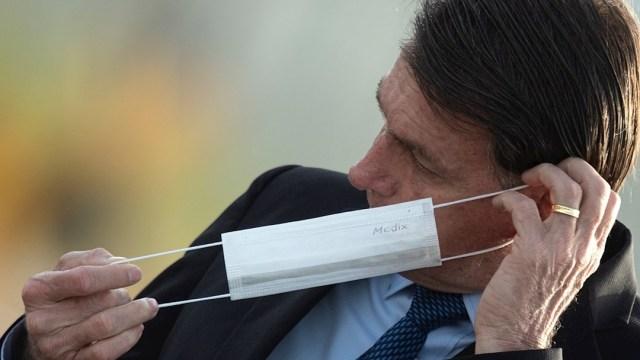 El presidente de Brasil, Jair Bolsonaro, se retira el cubrebocas
