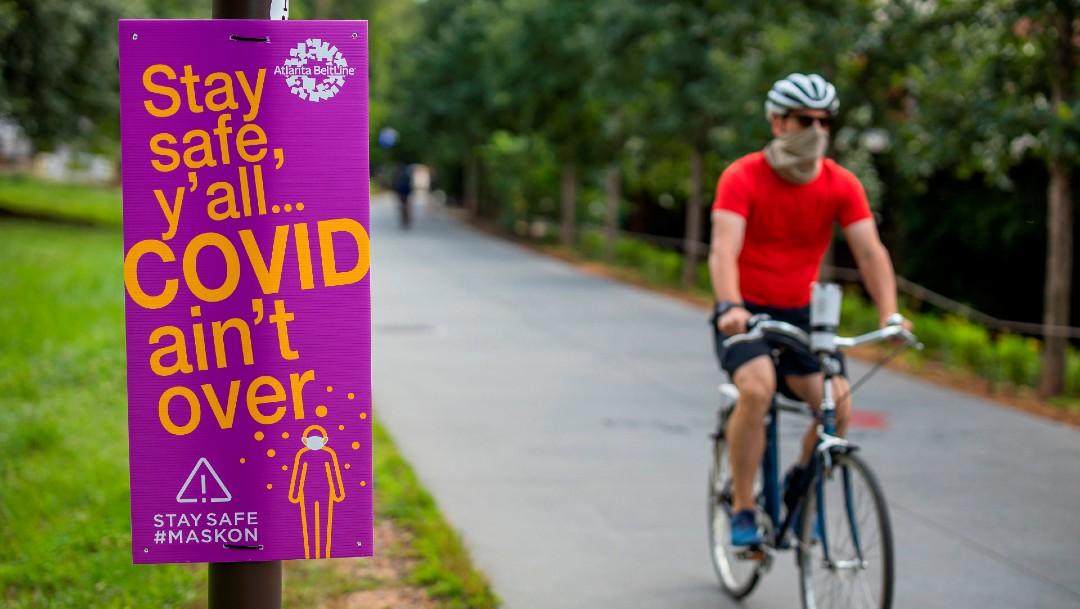 Ciclista en EEUU con cubrebocas; anuncian ensayo de vacuna