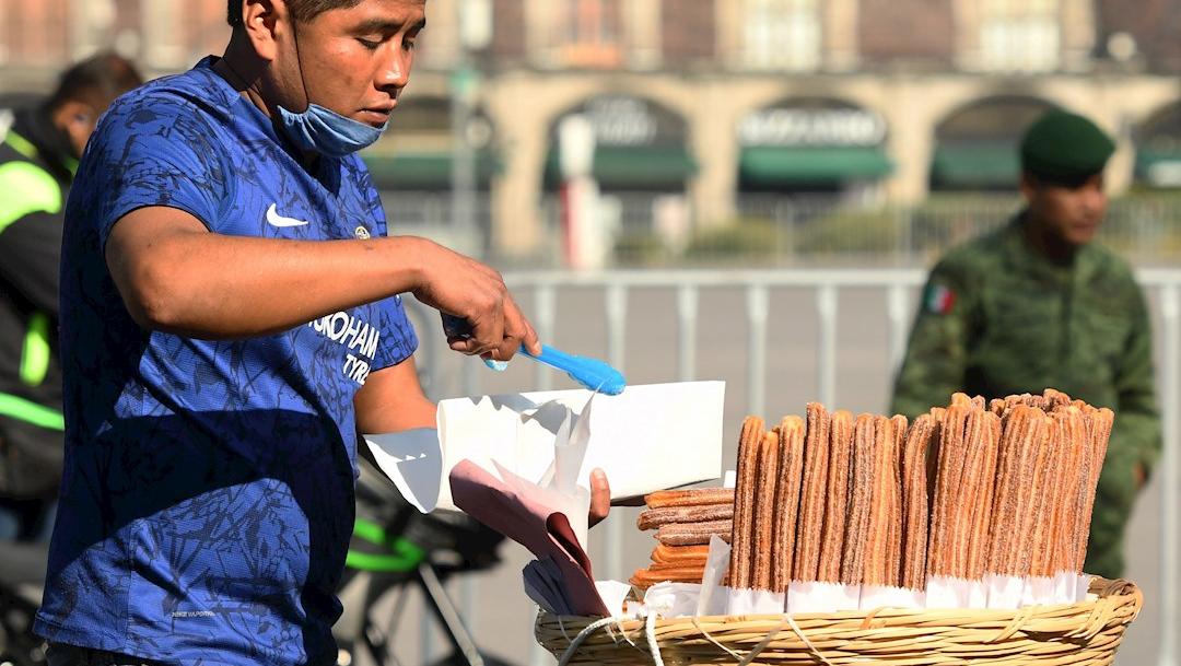 Un hombre vende churros en el centro histórico de la CDMX durante la pandemia por coronavirus. (Foto: EFE)