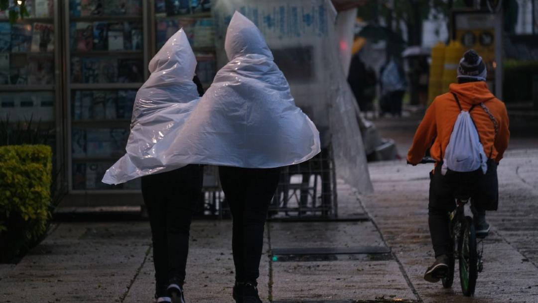 Transeúntes utilizan paraguas y rompe vientos para cubrirse de la lluvia