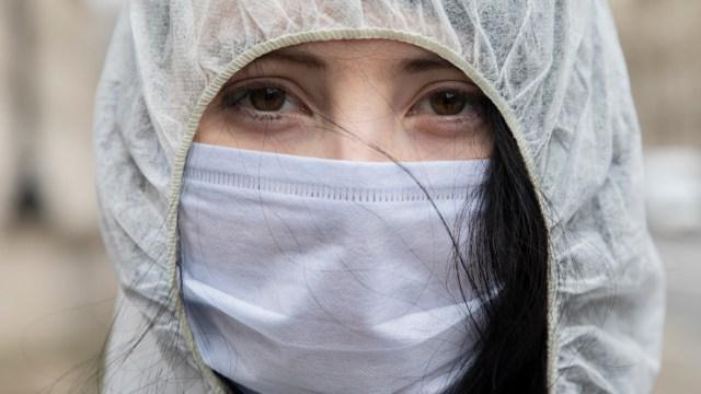Mujer usando cubrebocas, muertos por COVID en todo el mundo superan la barrera de los 560,000