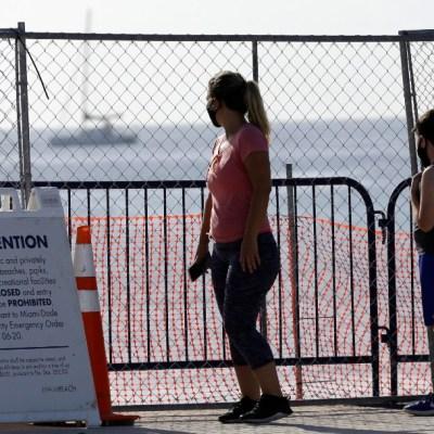 Personas con cubrebocas en Miami; Miami ordena toque de queda por coronavirus