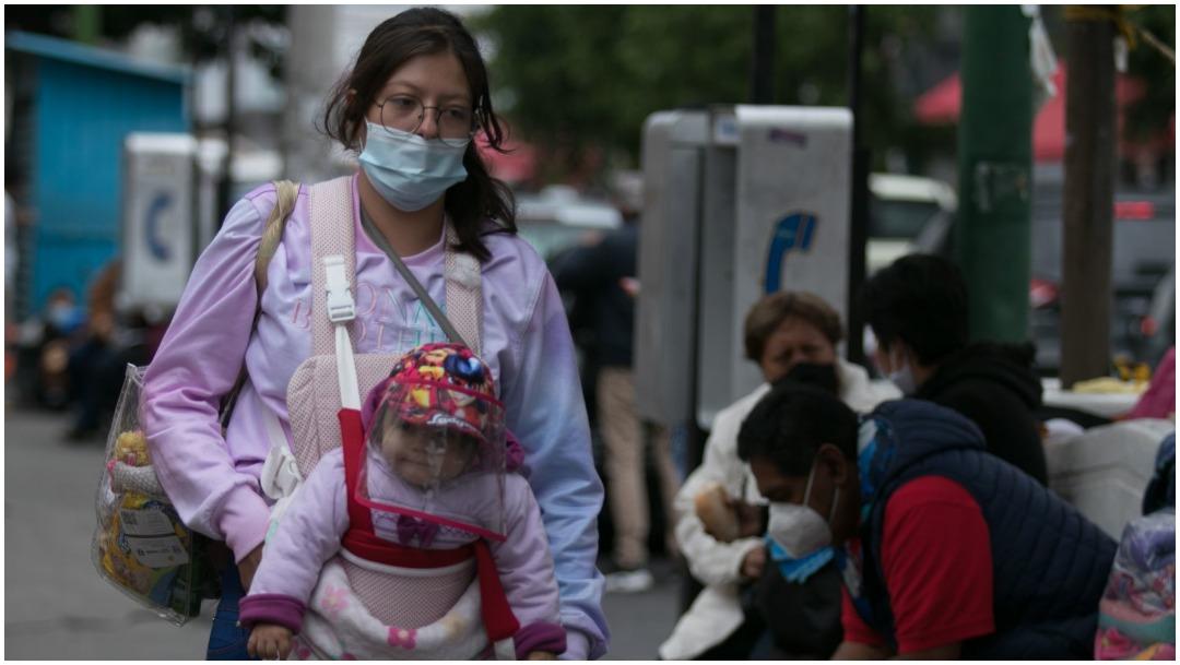 Mujeres caminan por calles de la CDMX usando cubrebocas