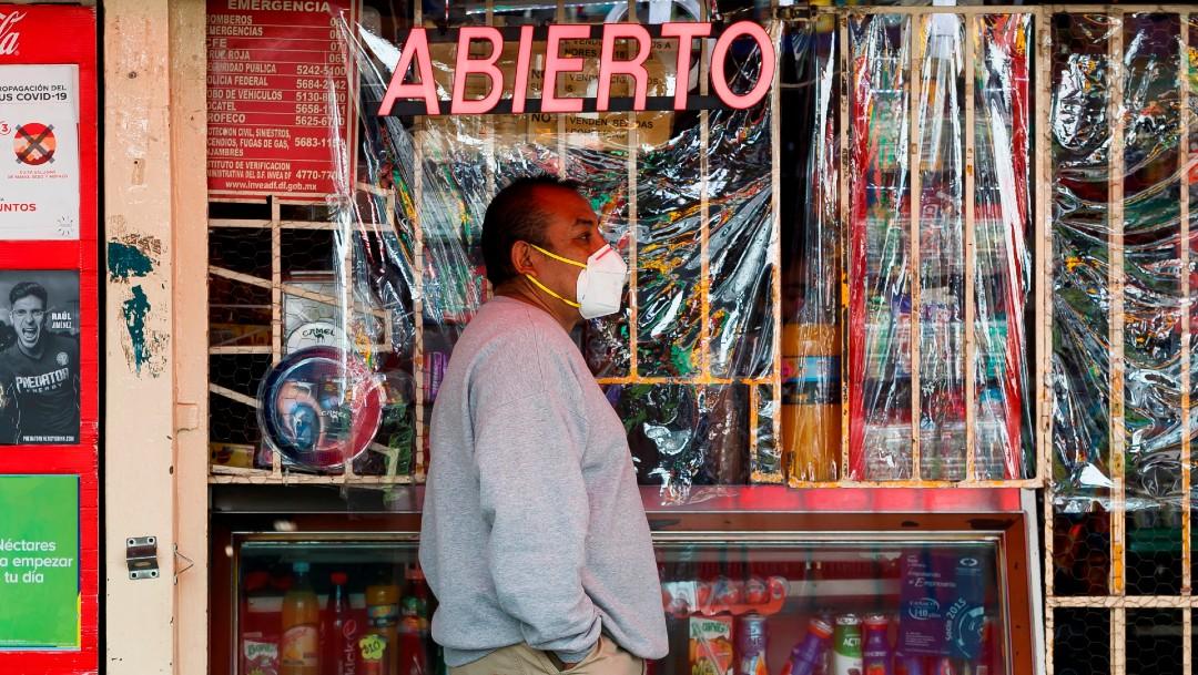Hombre con cubrebocas frente a una tienda en México