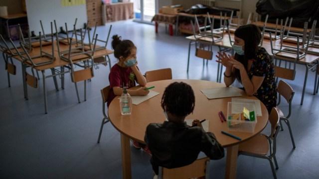 Niños y maestra con cubrebocas en escuela de Barcelona, España