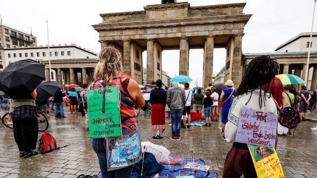 Manifestantes participan en una protesta contra las regulaciones de COVID-19, frente a la Puerta de Brandenburgo en Berlín, Alemania