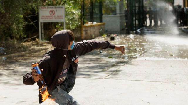Manifestante lanza bomba Molotov a miembros de la Guardia Nacional Mexicana durante una protesta en Chihuahua