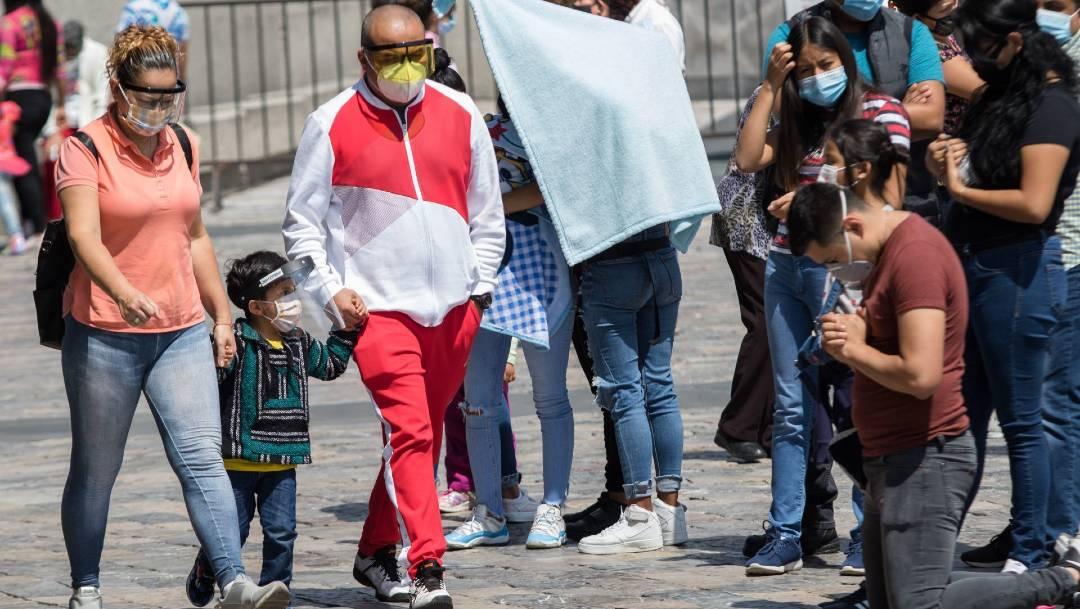 Fotografía de ciudadanos caminando con caretas y tapabocas
