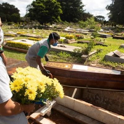 Empleados de un panteón en Brasil bajan el cuerpo de una víctima de COVID-19 para ser enterrado